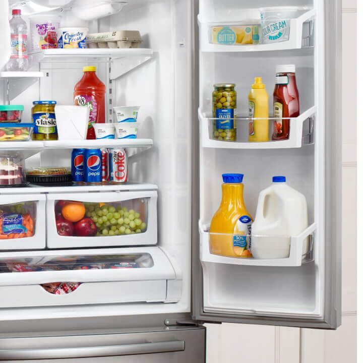 Open Amana® refrigerator with food inside