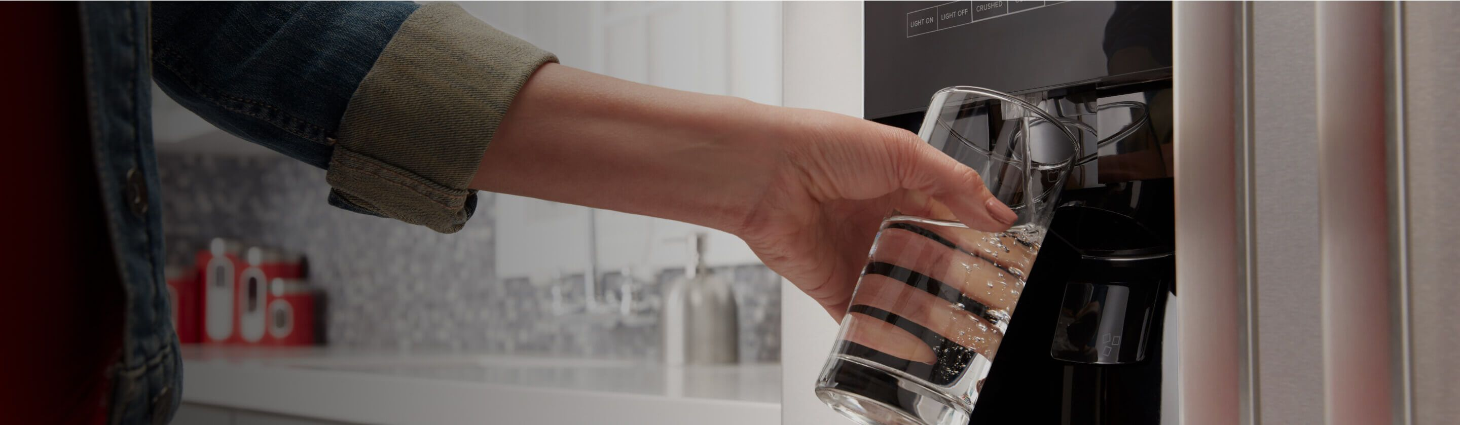Person filling a glass from a refrigerator water dispenser