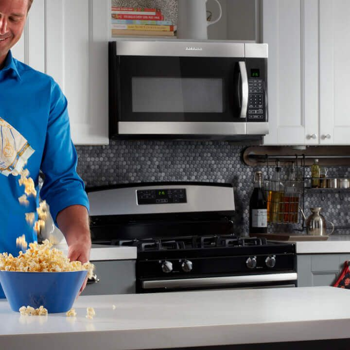 Person pouring popcorn into bowl in kitchen with Amana® range and microwave