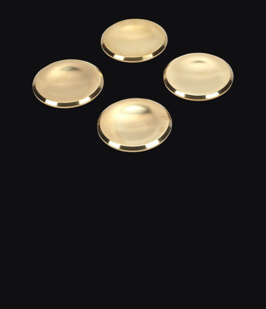Brass burner caps isolated on a black background.