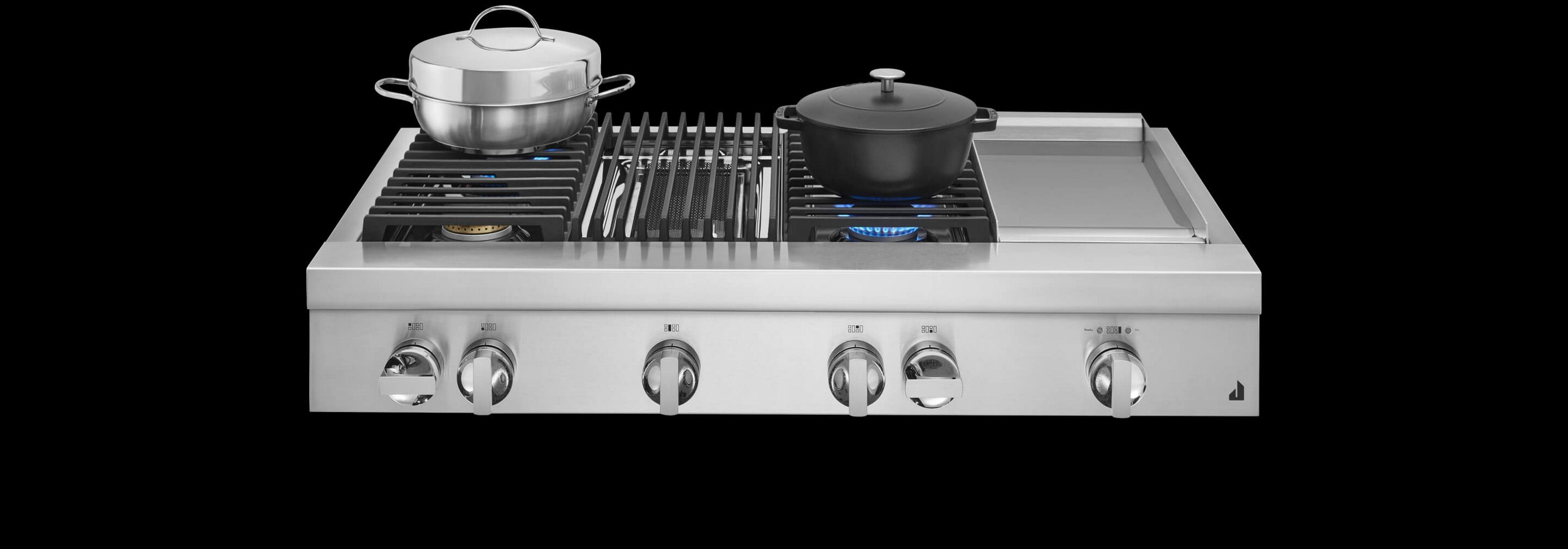 A JennAir® Professional-Style Range in NOIR™ Design, with stainless steel and cast iron pans atop lit burners.