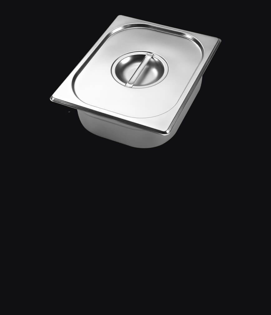 A warming pan with lid isolated on a black background.