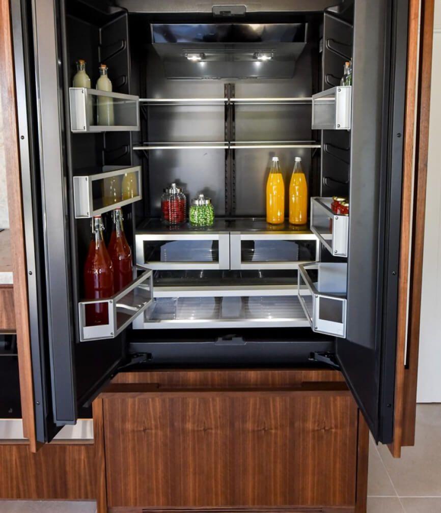 The lit Obsidian interior of a JennAir® Built-In Refrigerator.