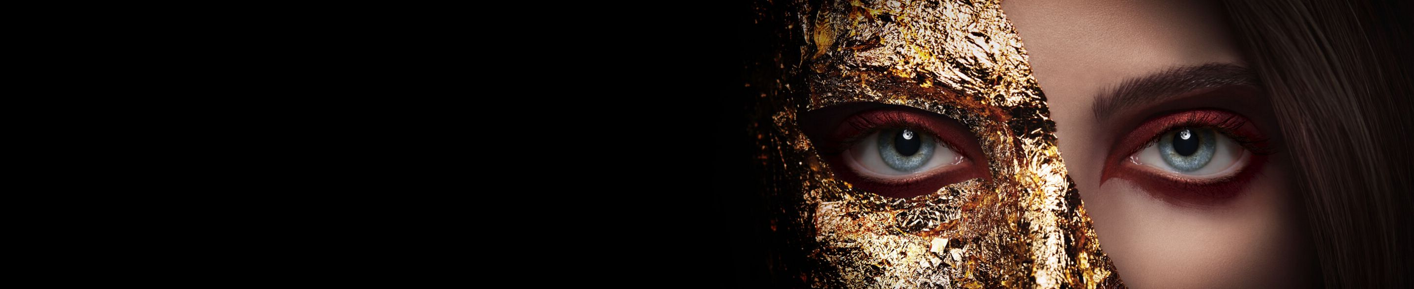 A woman's face half obscured by golden foil.
