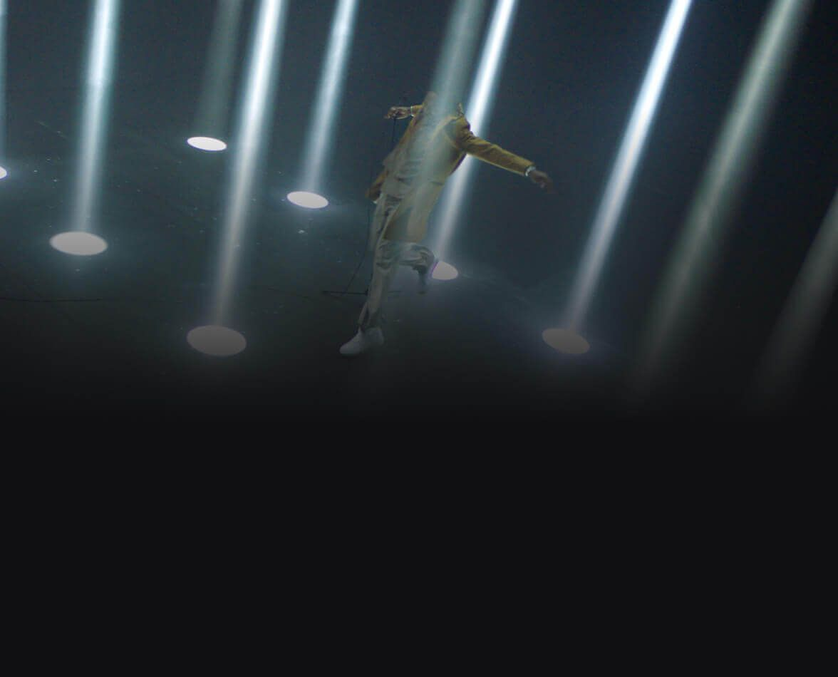 A man standing surrounded by beams of light.