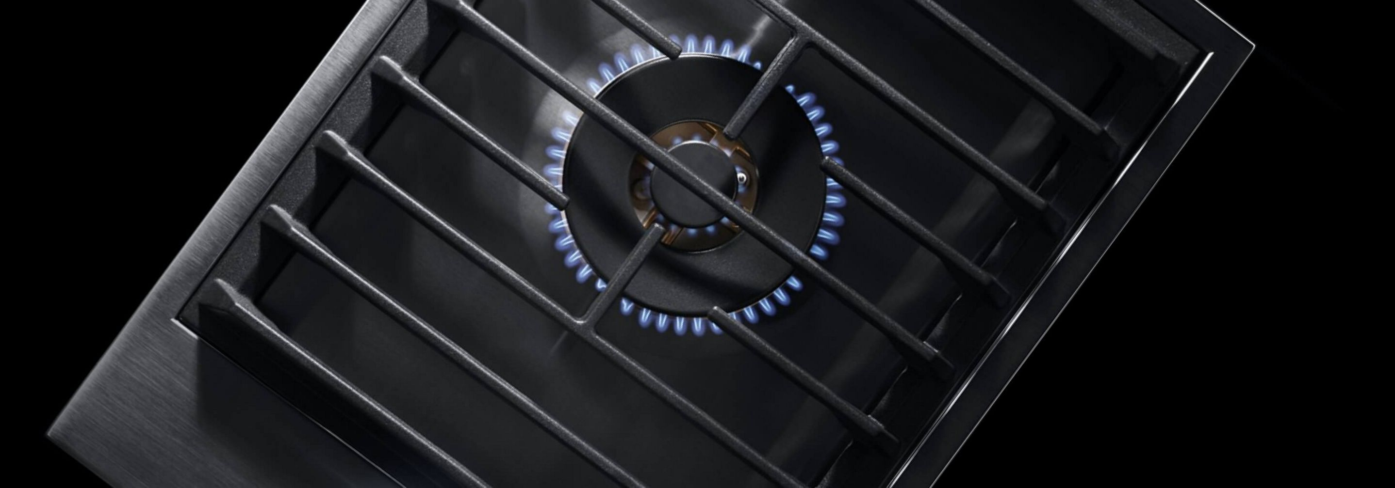A lit 1-burner gas cooktop with wok ring.