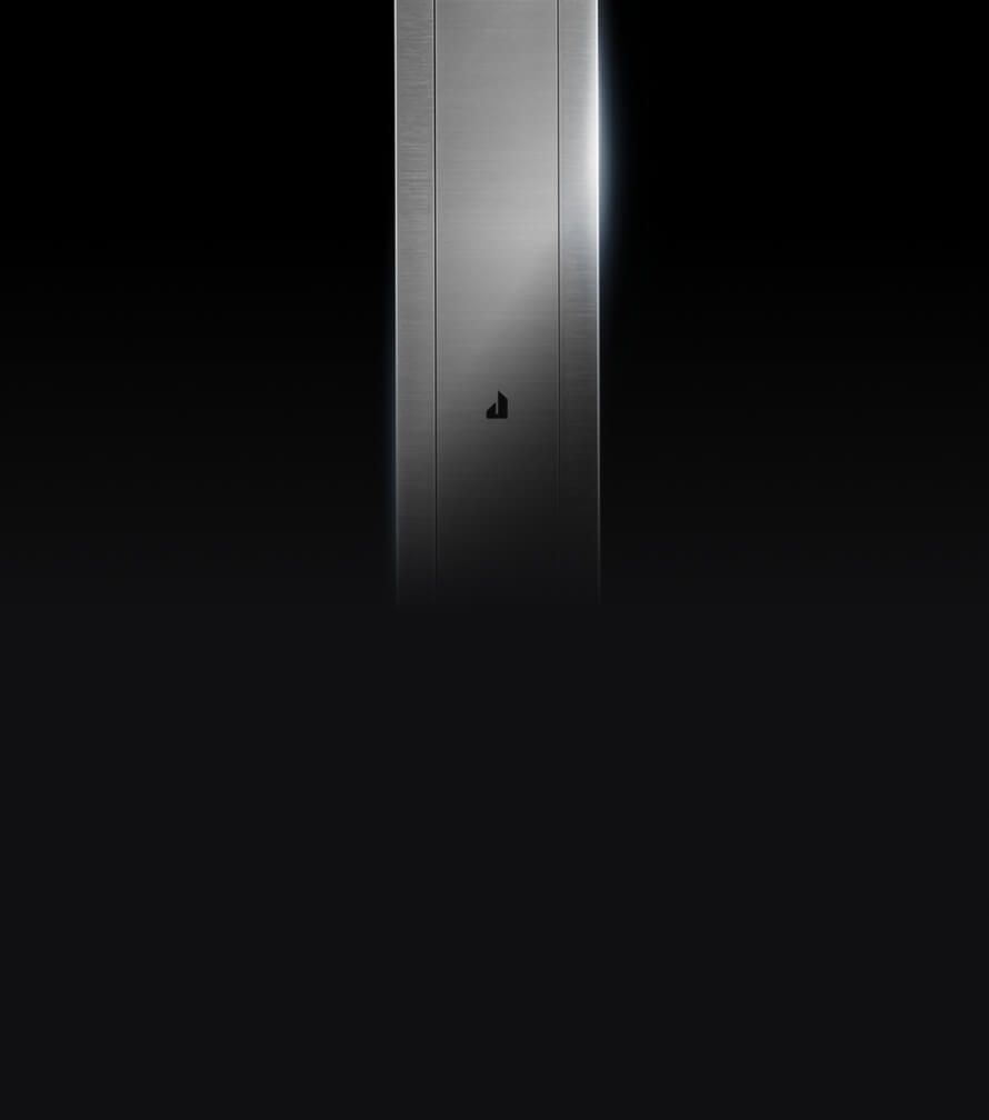 The sleek stainless downdraft vent isolated on a black background.