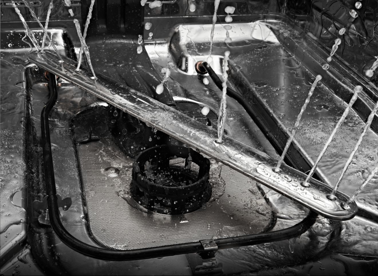 The interior of a JennAir® dishwasher, showing the bottom wash arm.