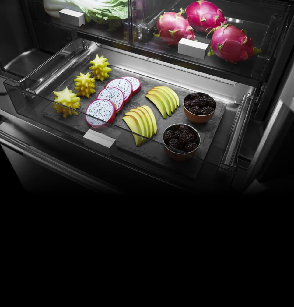 Bright light shining on colorful food inside a refrigerator drawer
