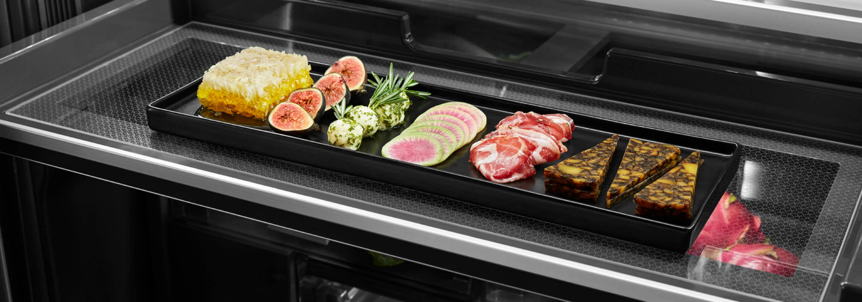 A charcuterie board with fruits, vegetables, meat and cheese inside the Gourmet™ Bay Drawer