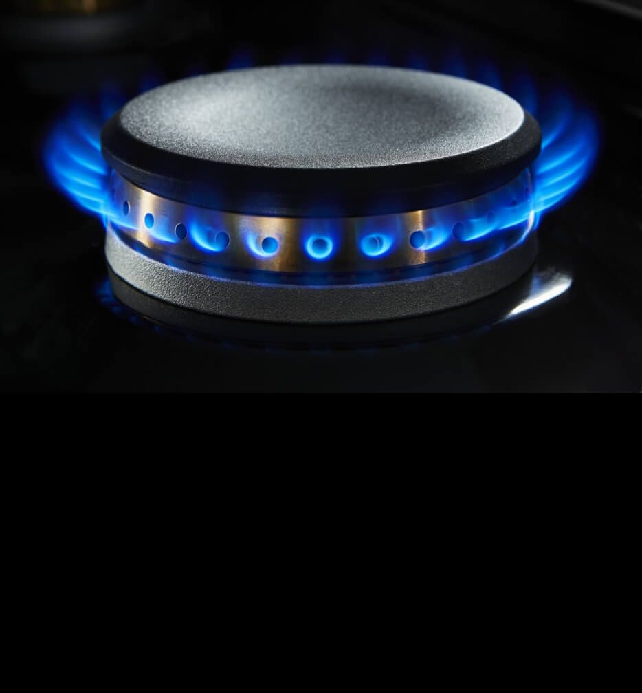 A lit dual-stacked burner on a gas rangetop.
