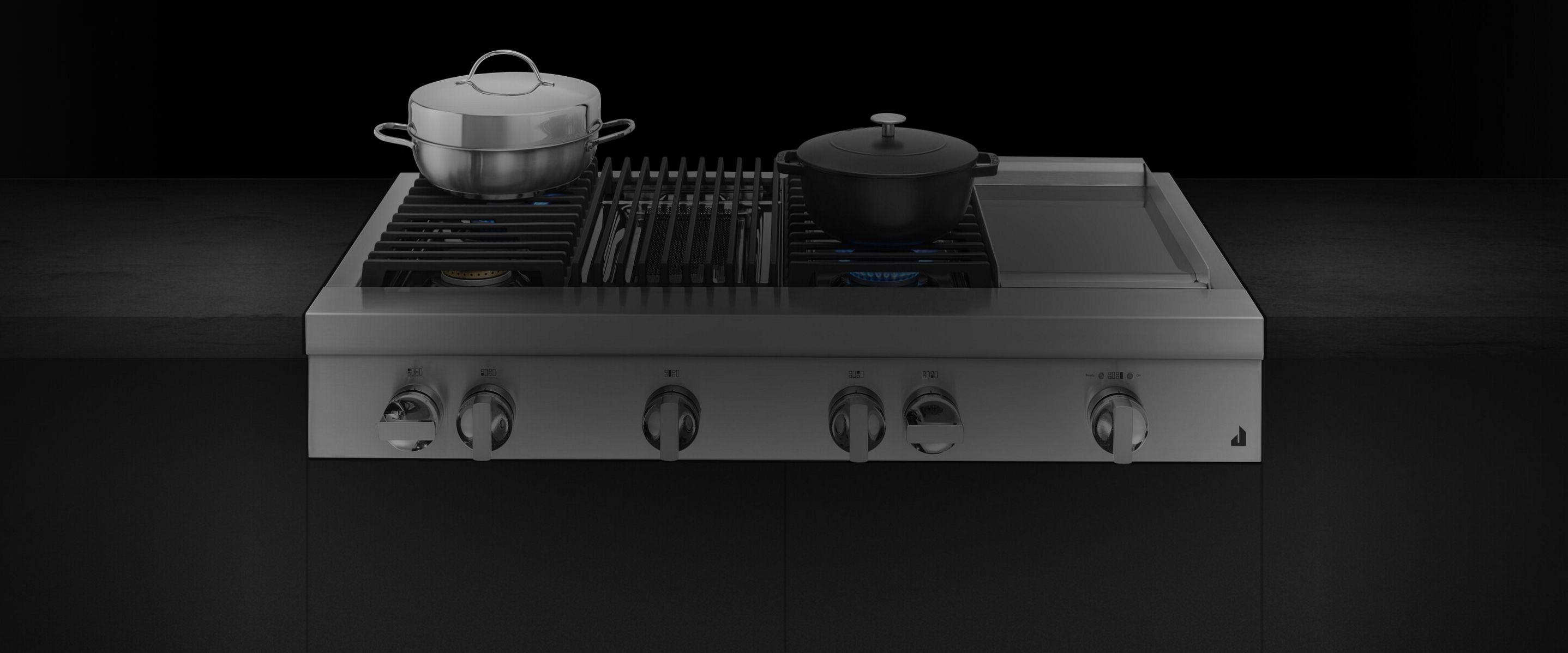 A JennAir® NOIR™ Design rangetop with pans and cookware on top.