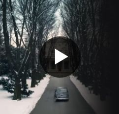 A car driving down a long driveway to a mansion surrounded by snow.
