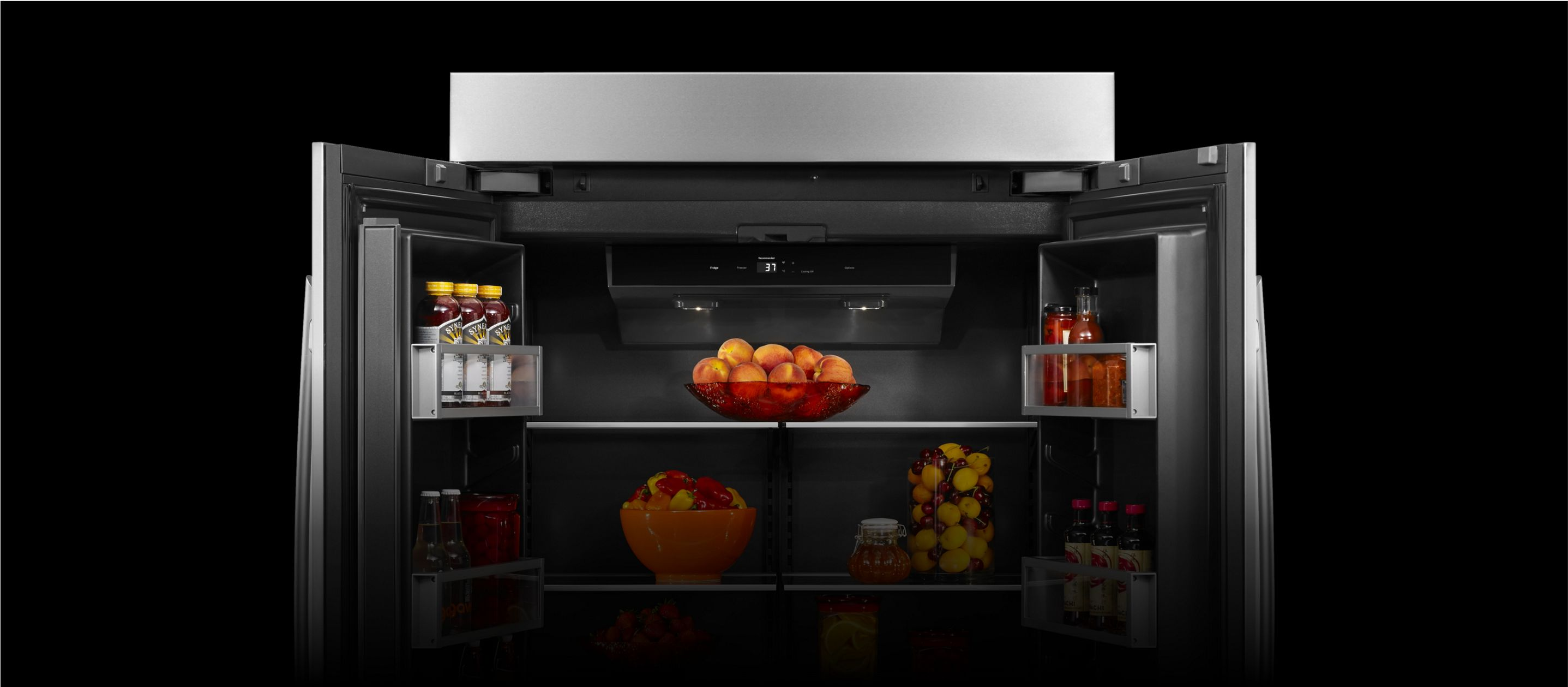 An open JennAir[®] high-end built-in refrigerator filled with vibrant orange fruit.