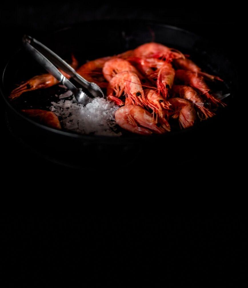 Colorful steamed shrimp in an ice bath.