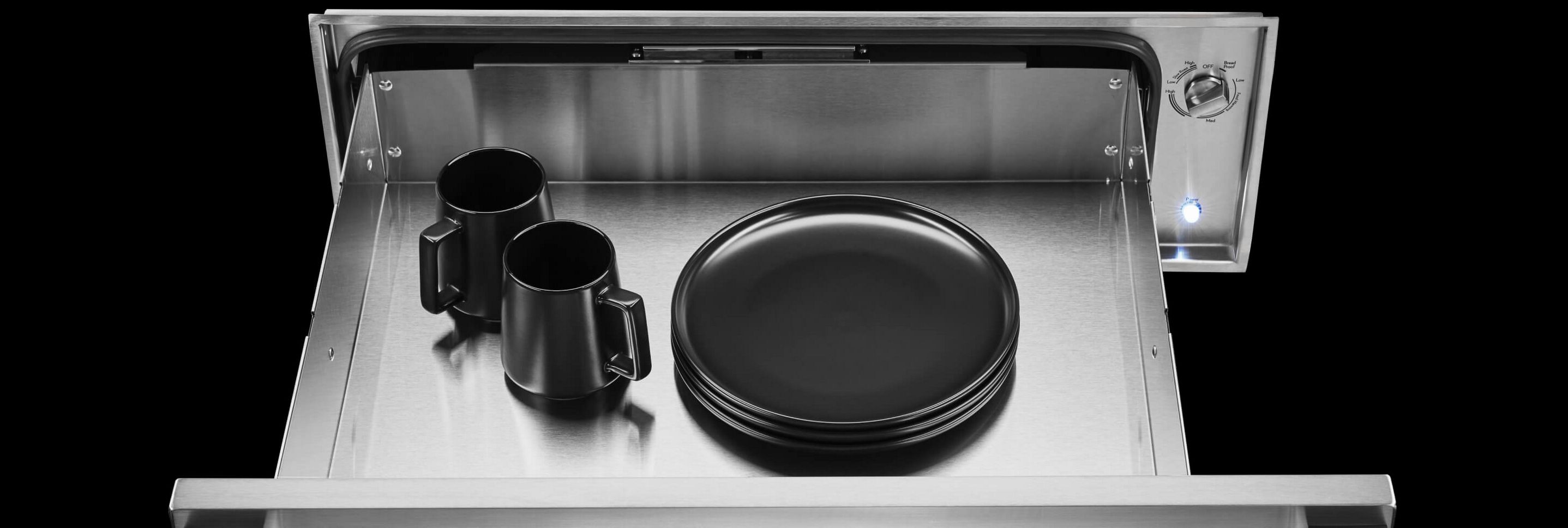 An open JennAir® warming drawer with black plates and mugs inside.