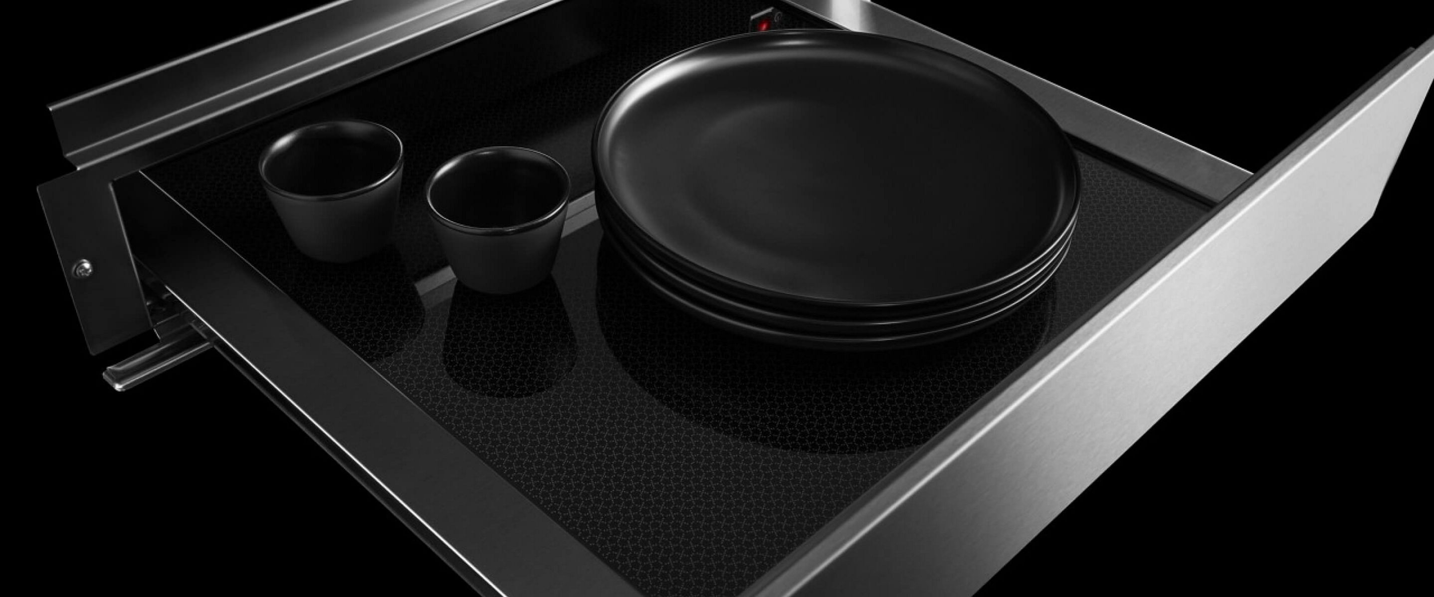 An open JennAir® warming drawer filled with plates and mugs.
