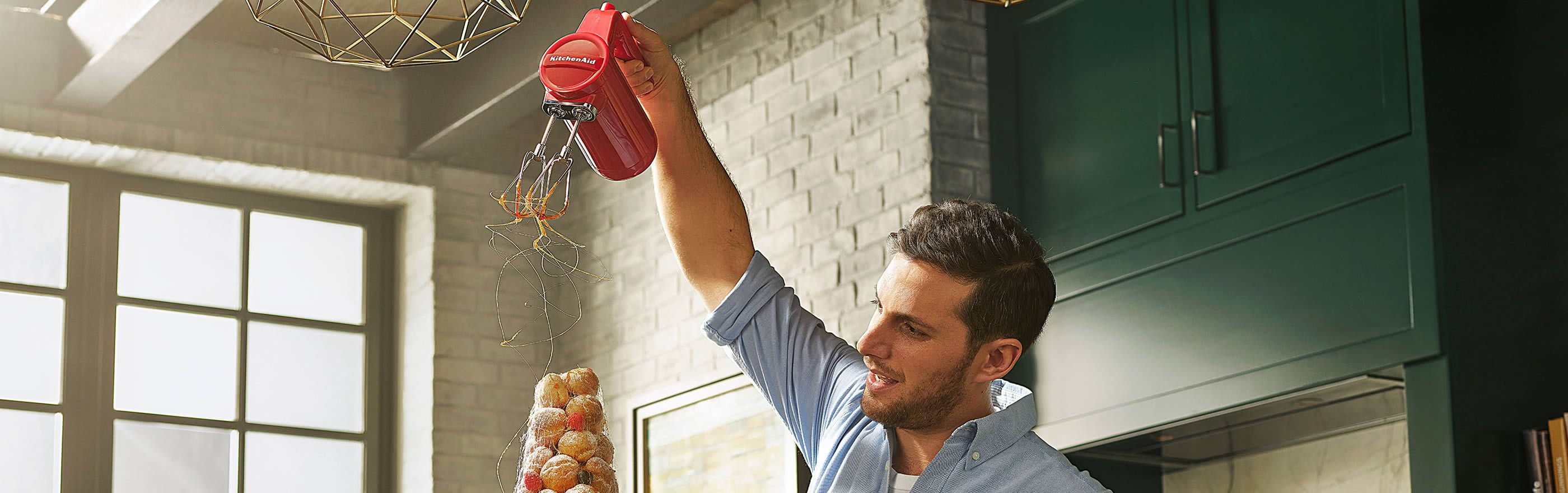 Man pours spun caramel over croquembouche from the beaters of a red KitchenAid Cordless Hand Mixer.