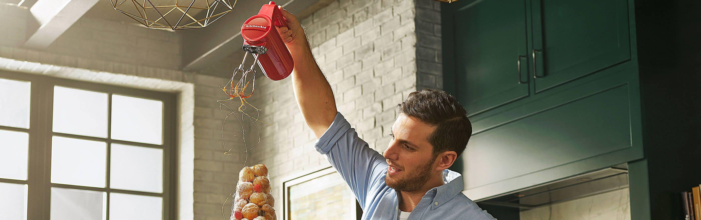 Homme versant des fils de caramel à l'aide d'un batteur à main rouge KitchenAid sur une pièce montée.