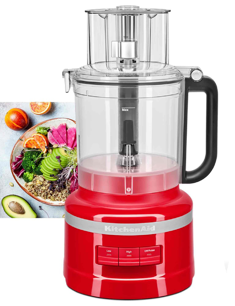 Front: KitchenAid Food Processor in Red. Background: half an avocado, half an orange, a peach and a meal in a bowl containing sliced avocado, orange wedges, brown rice, broccoli, purple cabbage