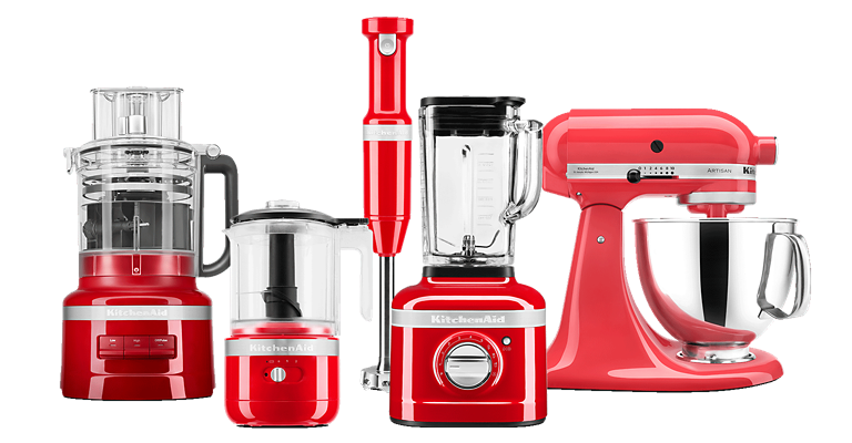 Line of KitchenAid countertop appliances and an immersion hand blender, all in red, including (from right to left) food processor, food chopper, blender and stand mixer.