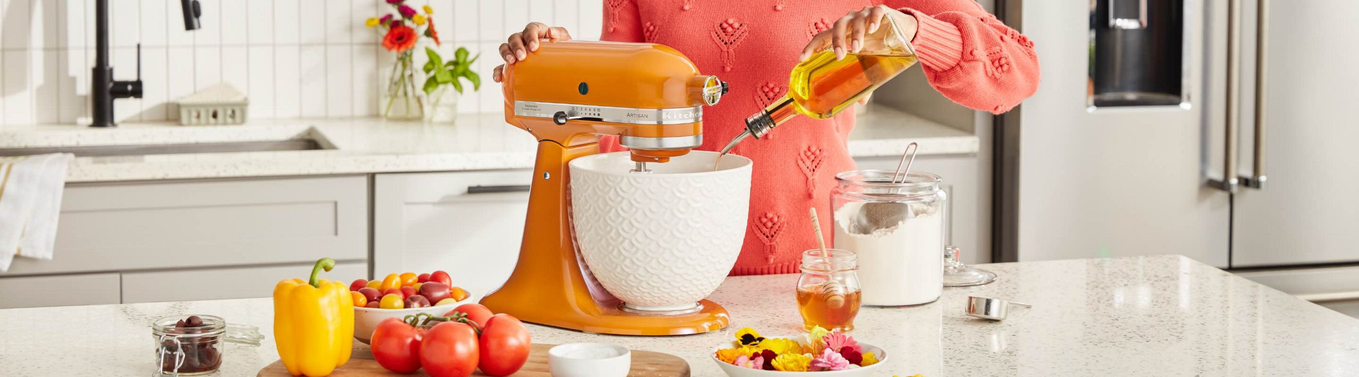 A woman pours cooking oil into the bowl of a KitchenAid stand mixer in Honey colour. On a cutting board next to the stand mixer are a bowl of cherry tomatoes, tomatoes on the vine, a yellow pepper and a bowl of salt. Also on the counter are a bowl of colourful flowers, a jar of honey, a glass container of flour with a measuring cup.