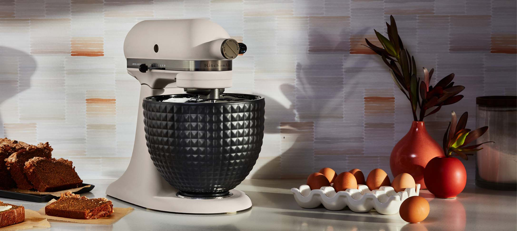 A Limited Edition Stand Mixer with a Stainless Steel Bowl surrounded by bread and eggs.