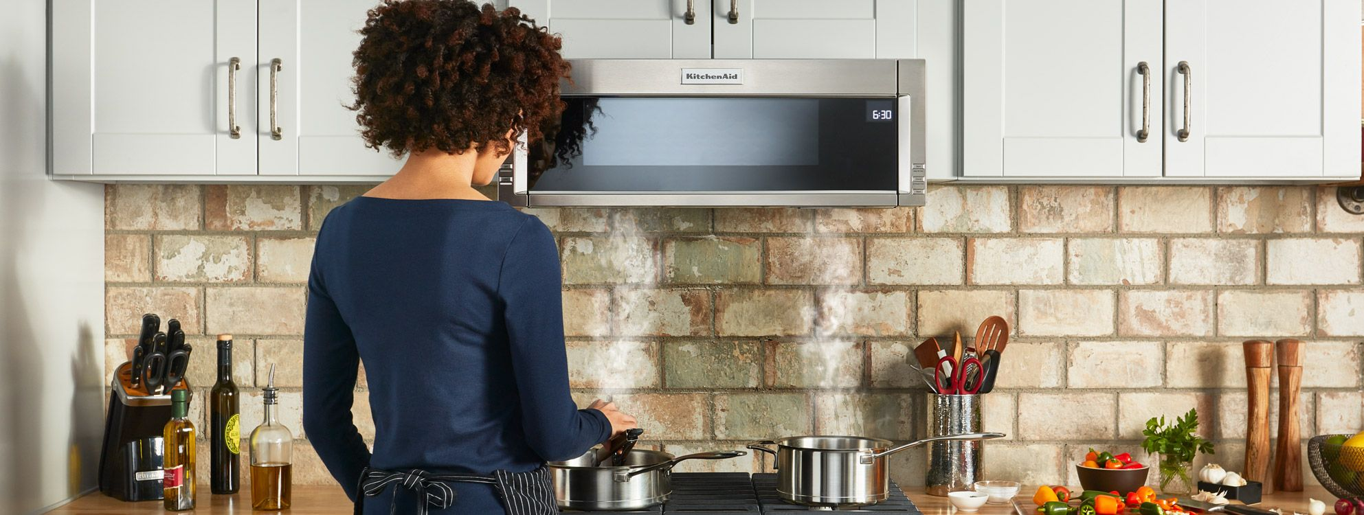 Woman cooking at KitchenAid oven range. In front is a KitchenAid microwave.