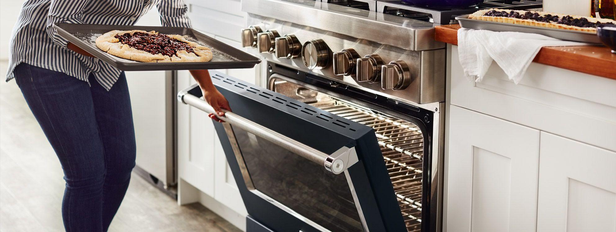 Personne ouvrant un four de cuisinière commerciale KitchenAid pour y insérer une plaque avec une tarte dessus