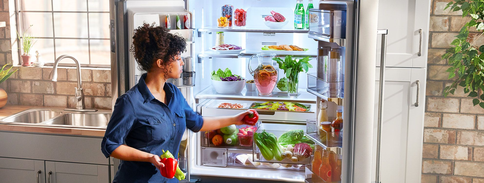 Woman reaches into opened KitchenAid refrigerator. Refrigerator is full of beverages, condiments, produce and cheeses.
