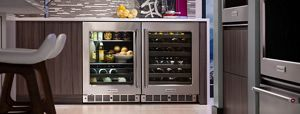 Large undercounter refrigerator filled with wine, beverages and a bowl of olives. On top of counter are limes and various liquor containers.