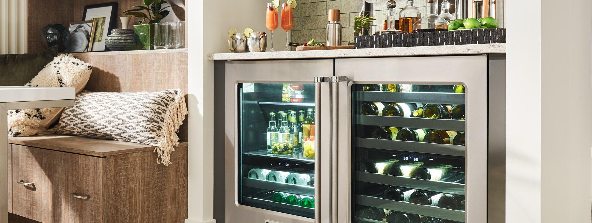 Grand réfrigérateur sous le comptoir rempli de bouteilles de vin, de boissons et d'un bol d'olives. Sur le dessus du comptoir se trouvent des citrons et autres contenants de liqueur