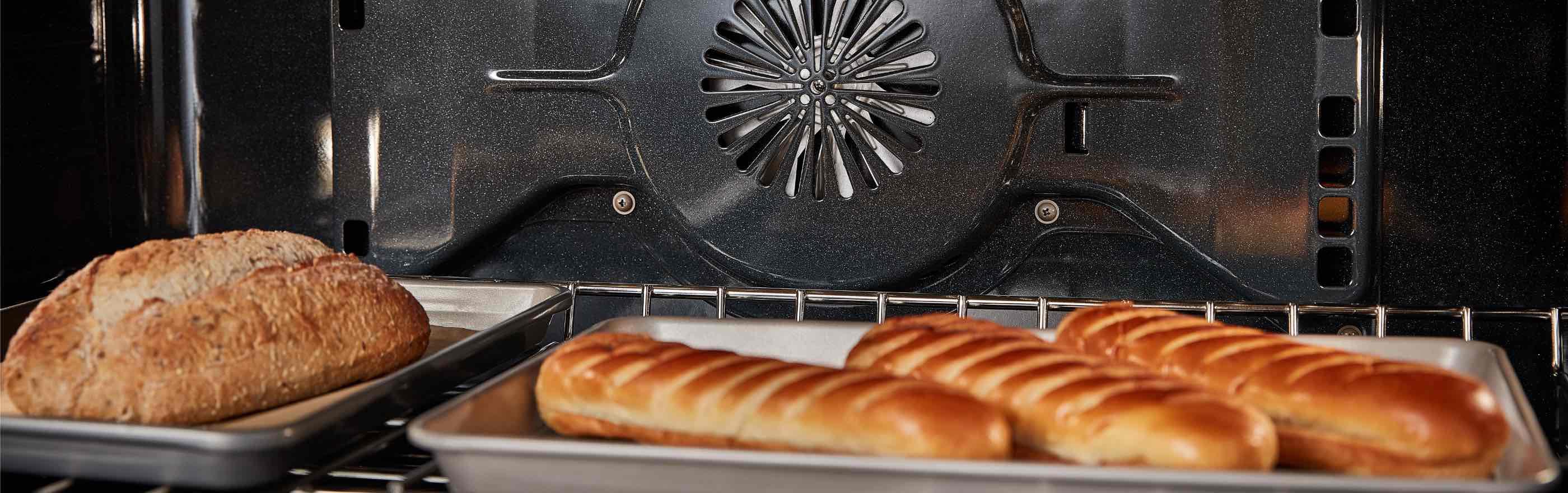 L'intérieur d'un four. Sur la grille se trouvent deux plaques de cuisson : l'une contient trois longues miches de pain et l'autre une seule miche de pain.
