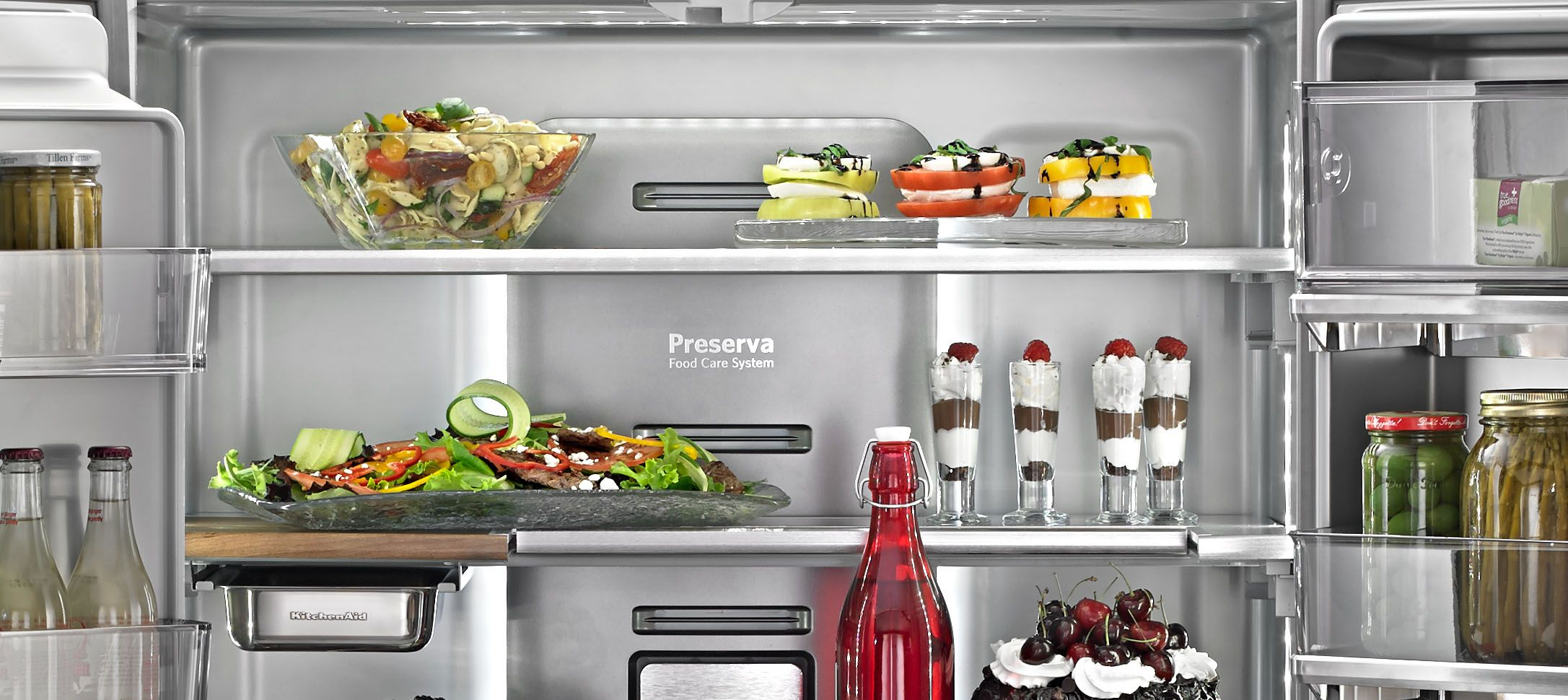 Inside of KitchenAid Refrigerator. Water, strawberries, salad and cake each in their own container.
