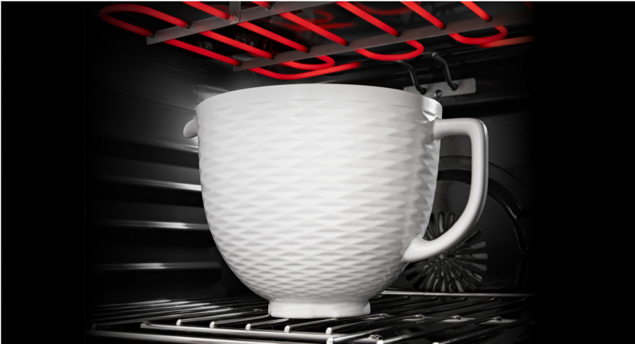 A KitchenAid® ceramic bowl placed in an oven.