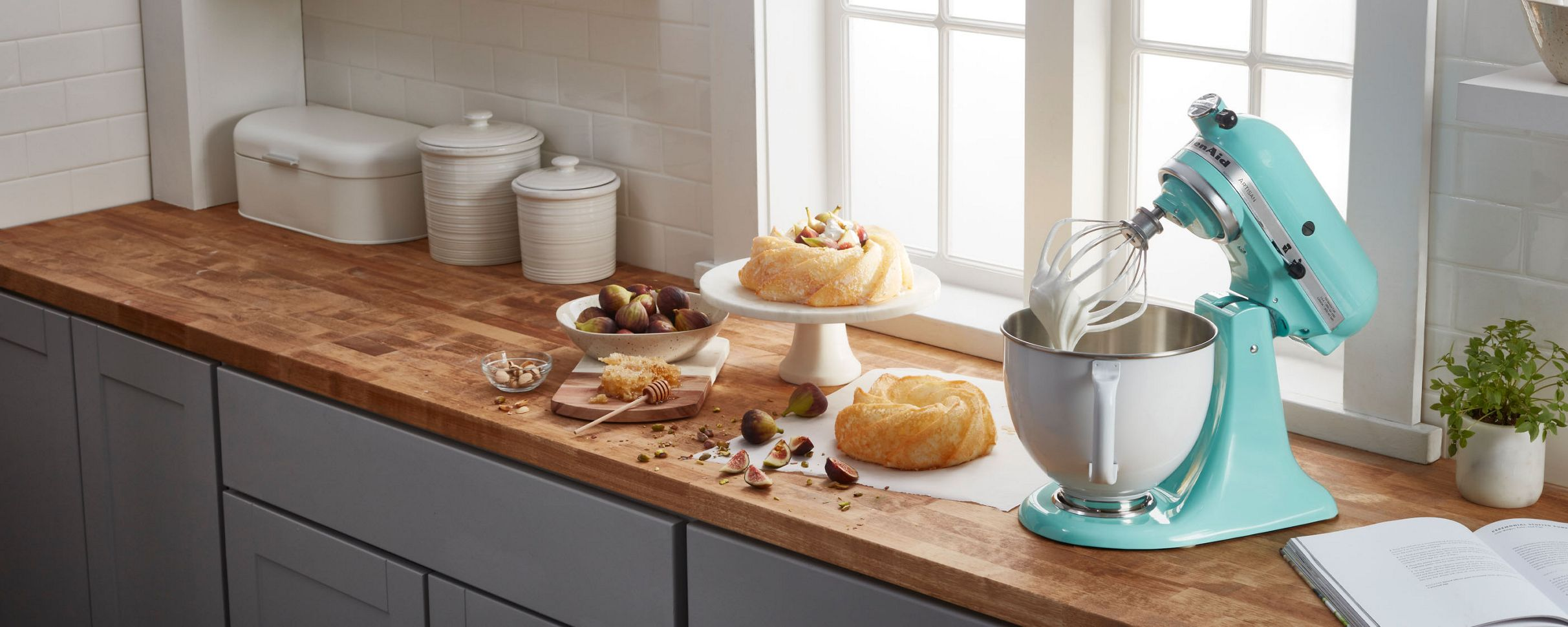 A tilt-head stand mixer with whipped cream surrounded by ingredients and pastries.