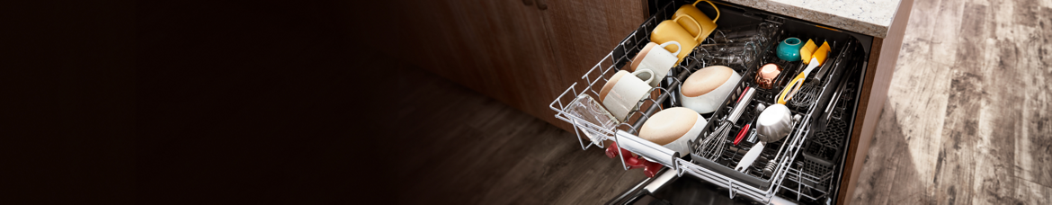 A top-down view of the fully loaded top rack in the KitchenAid FreeFlex(TM) Dishwasher — with bowls, mugs and large cooking utensils laying in neatly organized rows.