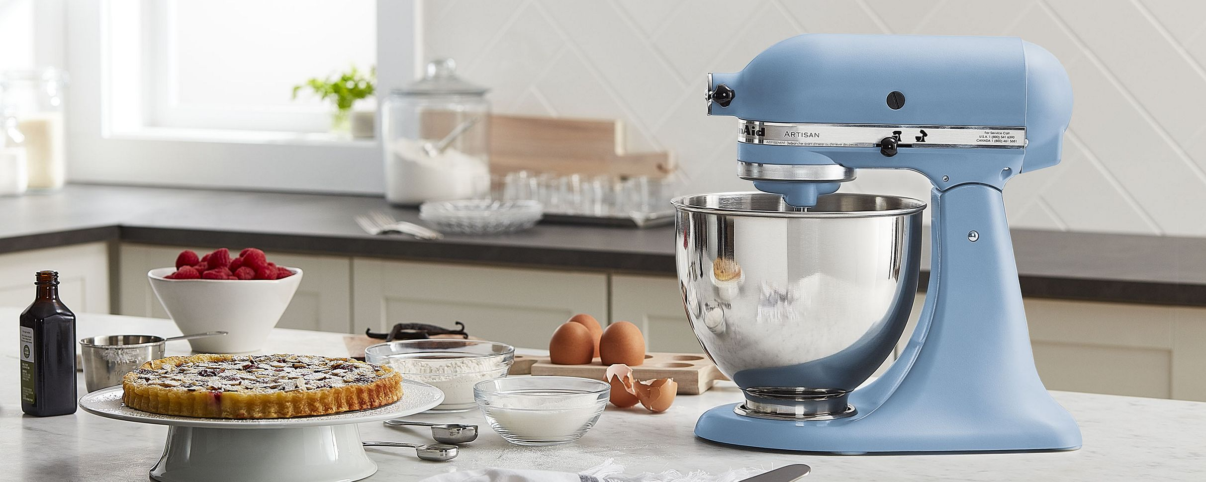 A red stand mixer with a transparent bowl, mixing ingredients