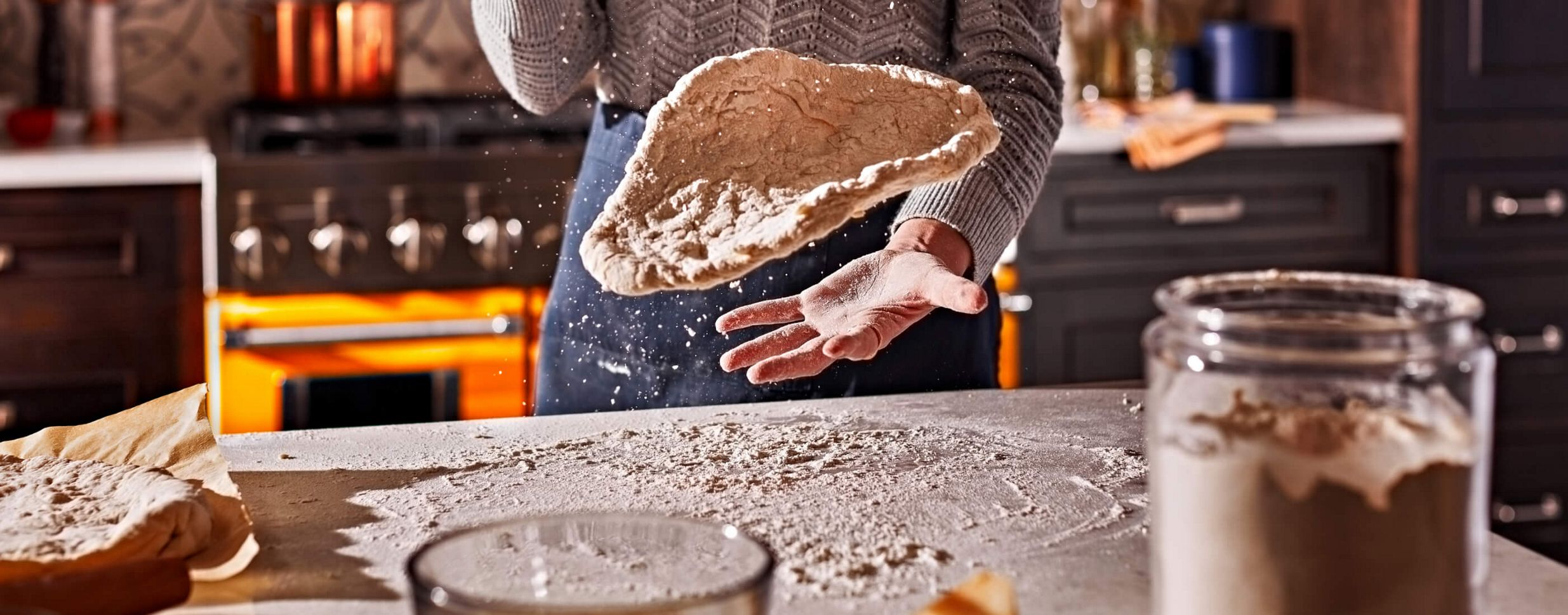 A maker expertly tossing well-floured pizza dough.