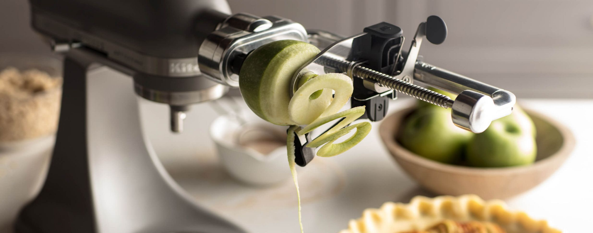 A Black Matte KitchenAid® Stand Mixer with a Spiralizer attachment holding a green apple.