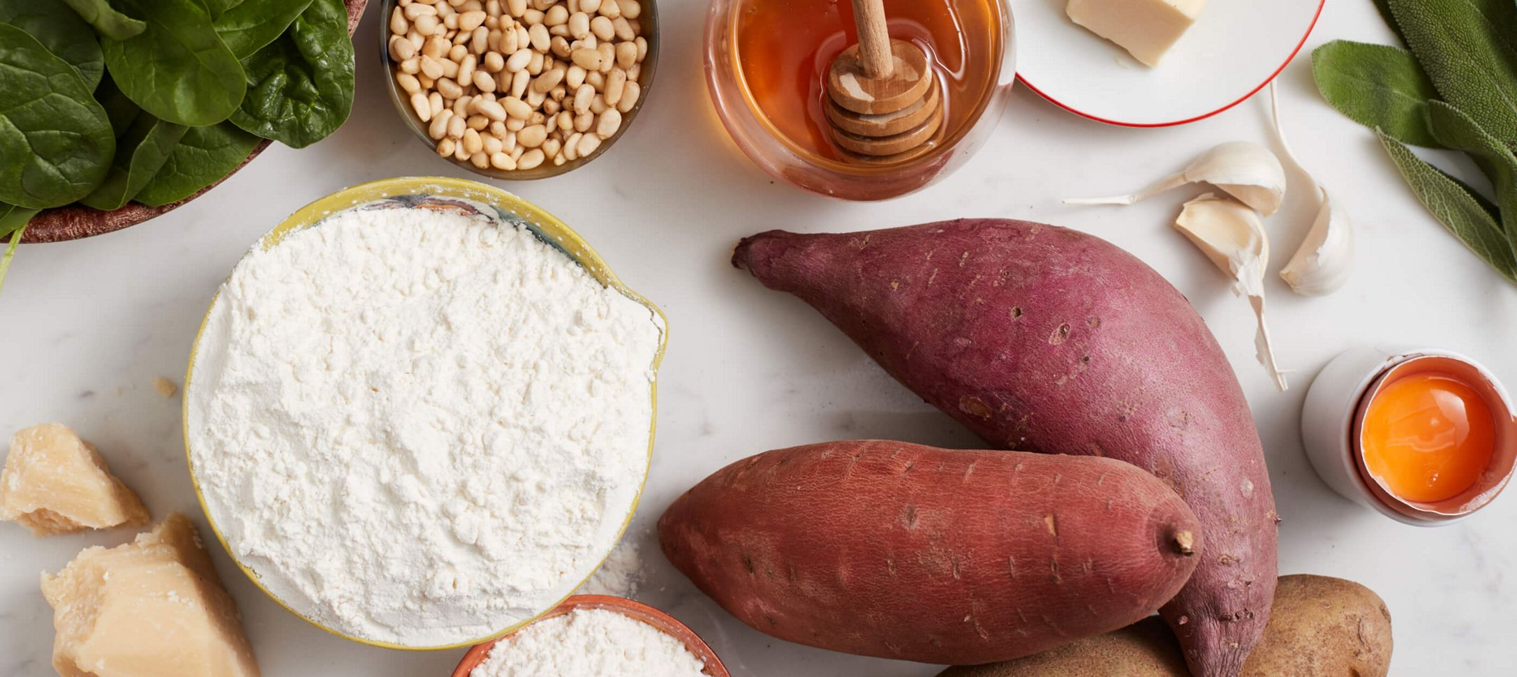 White Countertop with various ingredients, including fresh basil, garlic, flour, sweet potates, flour and honey