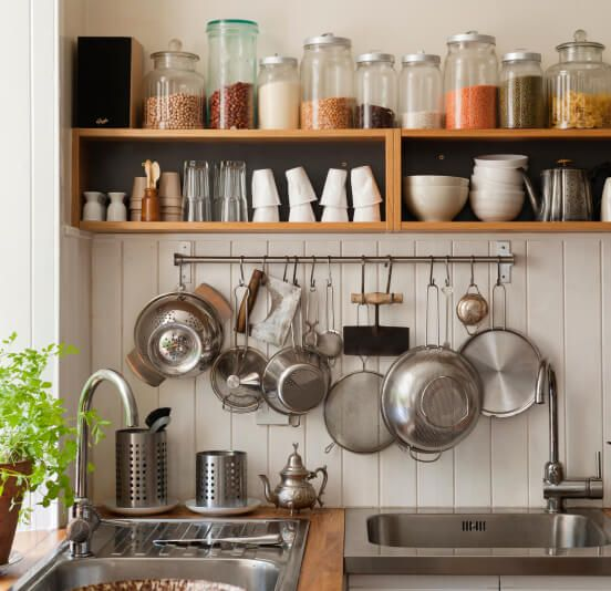 A kitchen filled with utensils, spices, dinnerware and more.