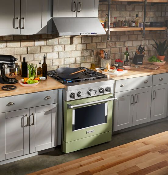 A sun-filled kitchen featuring an Avocado Cream Commercial-Style Range.