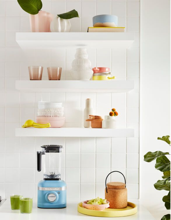 Clean white shelves adorned glasses, bowls and other kitchen utensils.