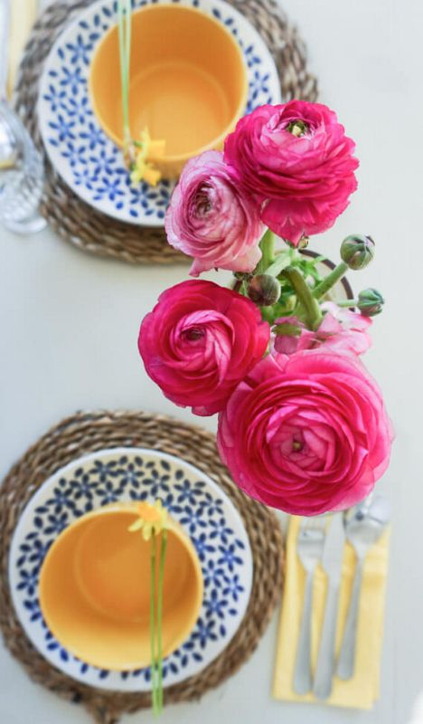 A set dinner table with large, pink flowers.