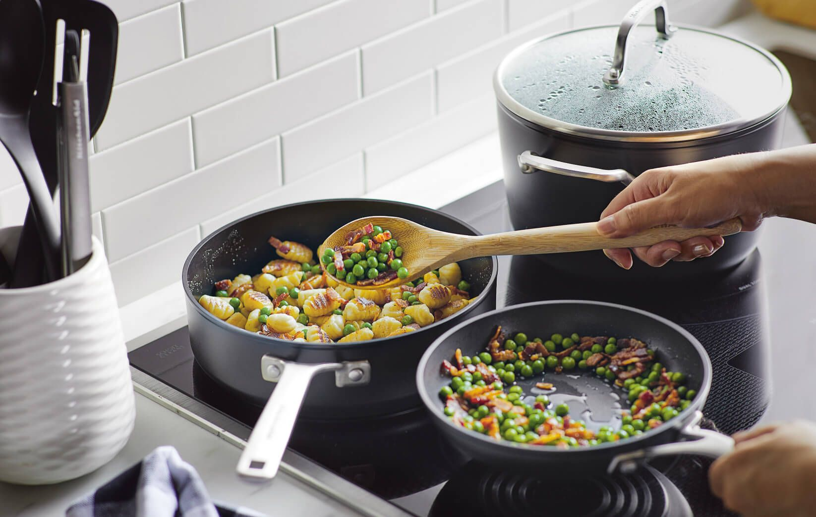 A person cooking with a hard-anodized induction pan.