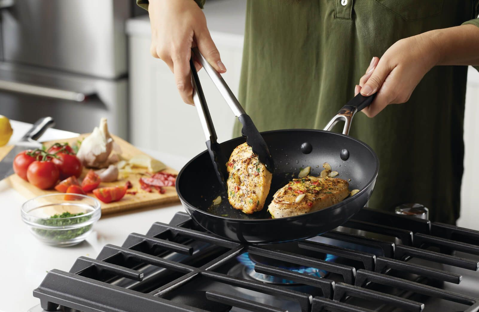 A person cooking with hard-anodized pans.