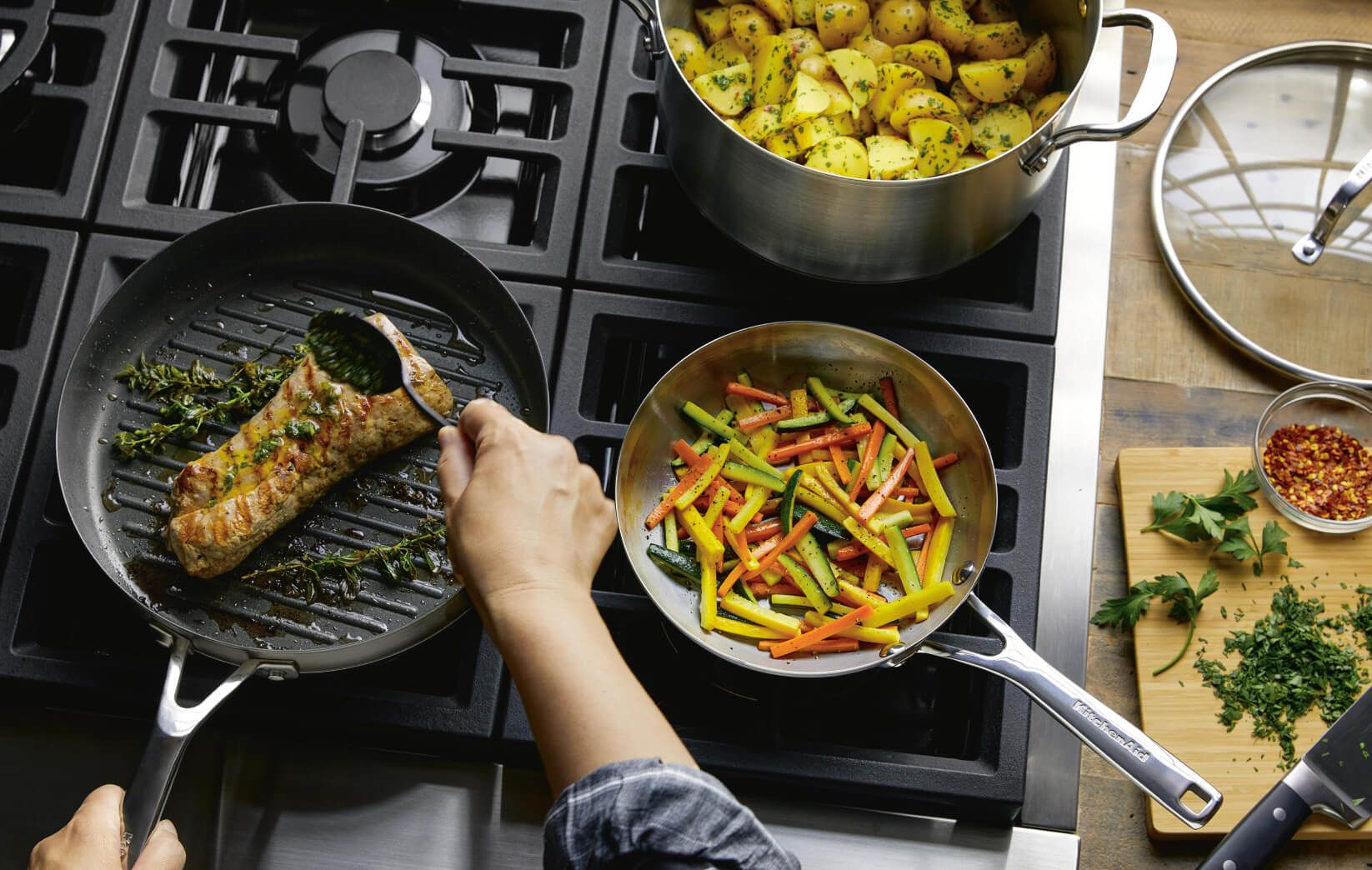 A person cooking with a stainless steel 3-ply base pan.