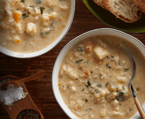 An overhead close-up of two bowls of cauliflower soup topped with fresh garnish.