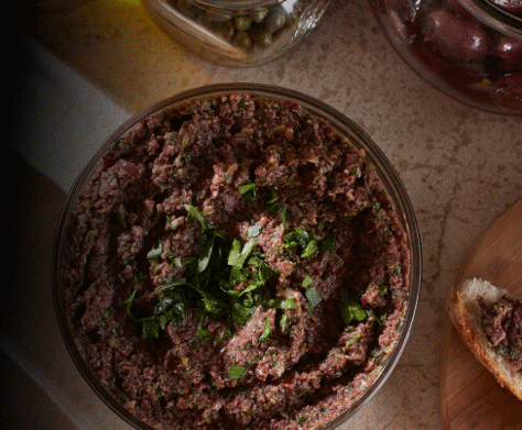 An overhead close-up of a creamy bowl of olive tapenade.